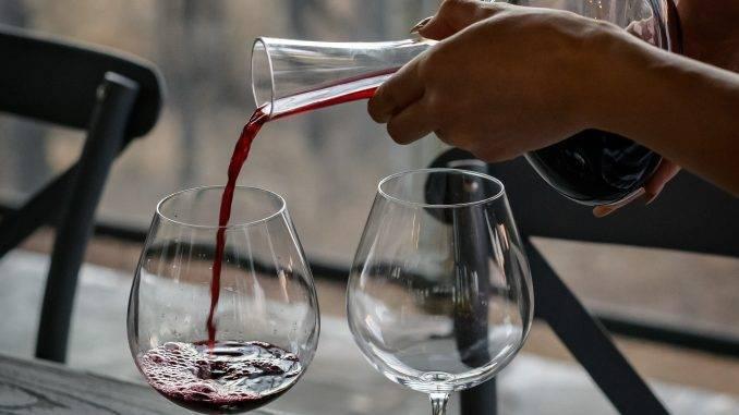 Des mains qui remplissent un verre de vin