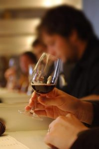 une personne en train de tester un vin dans un verre