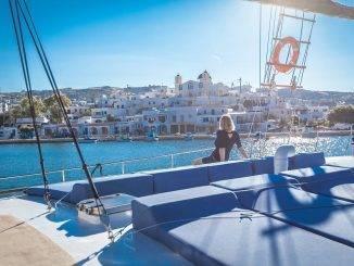 Femme sur le pont d'un bateau admirant la vue sur une île grecque