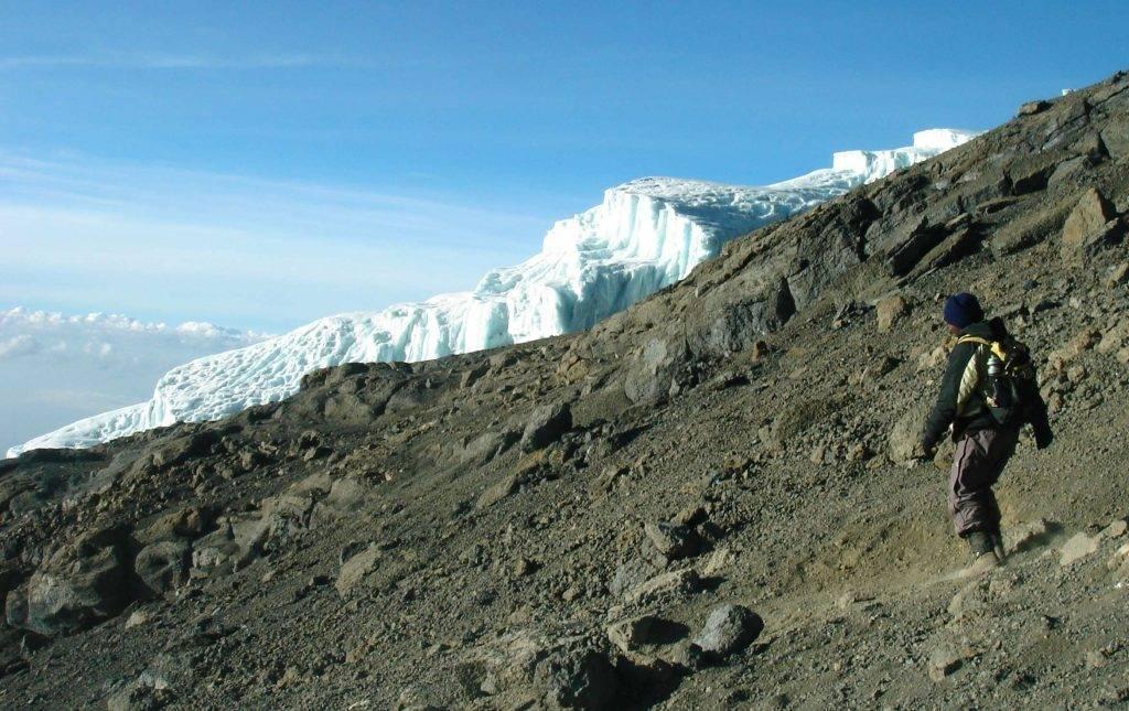 Personne faisant un trek en descente d'un sommet