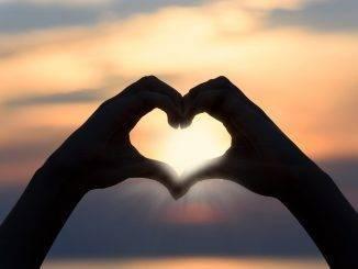 Coeur avec les mains sur fond de coucher de soleil