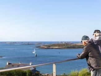 Seniors accoudés à une balustrade en train de contempler un paysage marin breton
