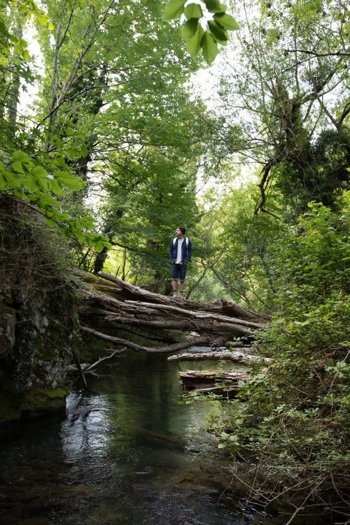Homme en train de traverser une rivière sur un tronc d'arbre